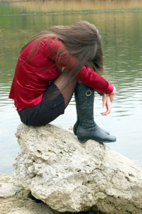 Woman sitting on rock by water looking sad